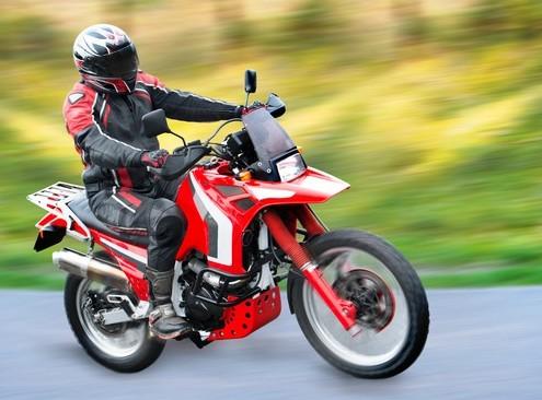Töff Fahrer auf rotem Motorrad in der Natur